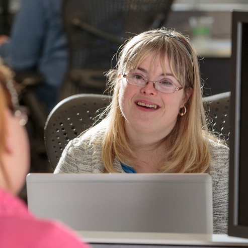 Young woman with Down Syndrome working at her computer in an office.