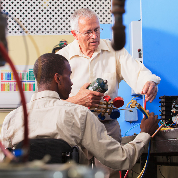 Instructor demonstrating air conditioner repair to a wheelchair user.