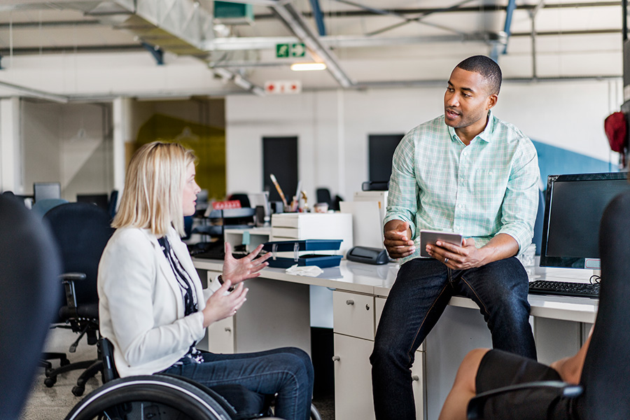 Businesswoman in a wheelchair sharing ideas with a coworker.
