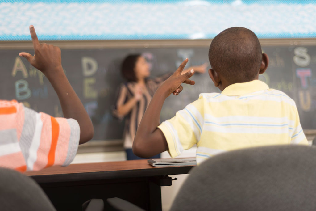 Student at a desk learning sign language.